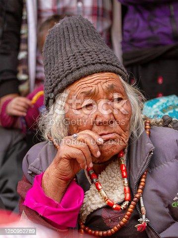 Lamayuru, India - June 17, 2012: Older gray-haired ladakhi women in traditional clothes and jewelry among the crowd of observers watching buddhist Yuru Kabgyat festival performance in the Lamayuru monastery