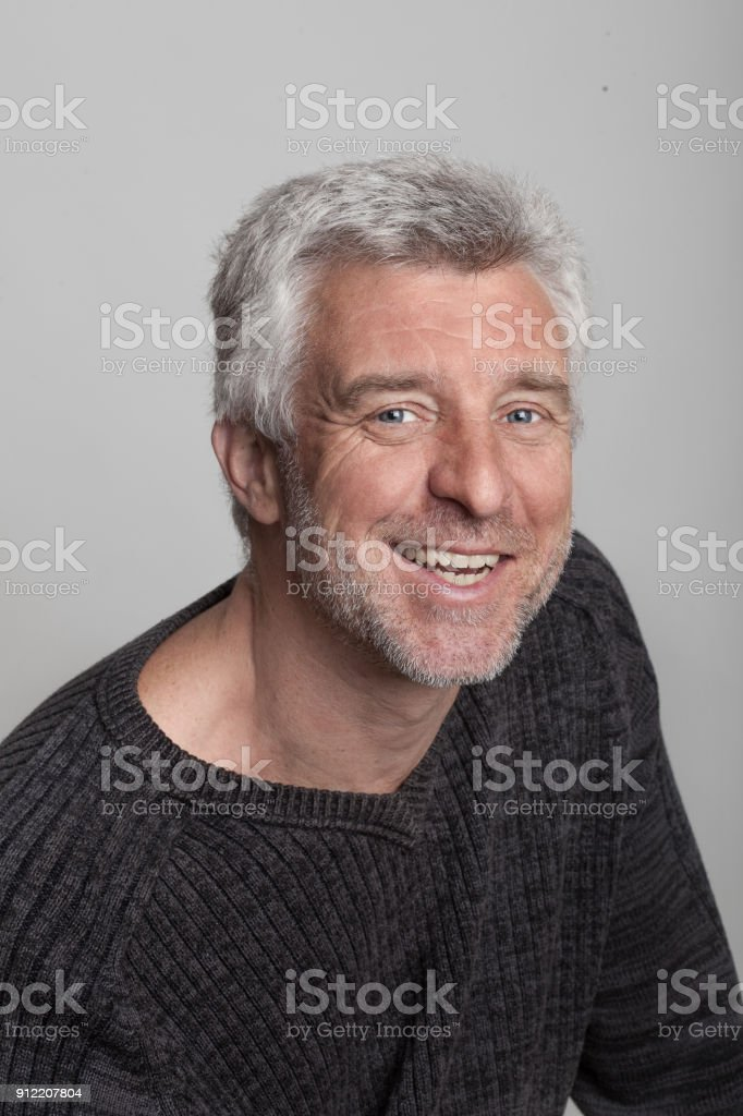 older gray-haired man sitting smiling looking at the camera grey eyes stock photo