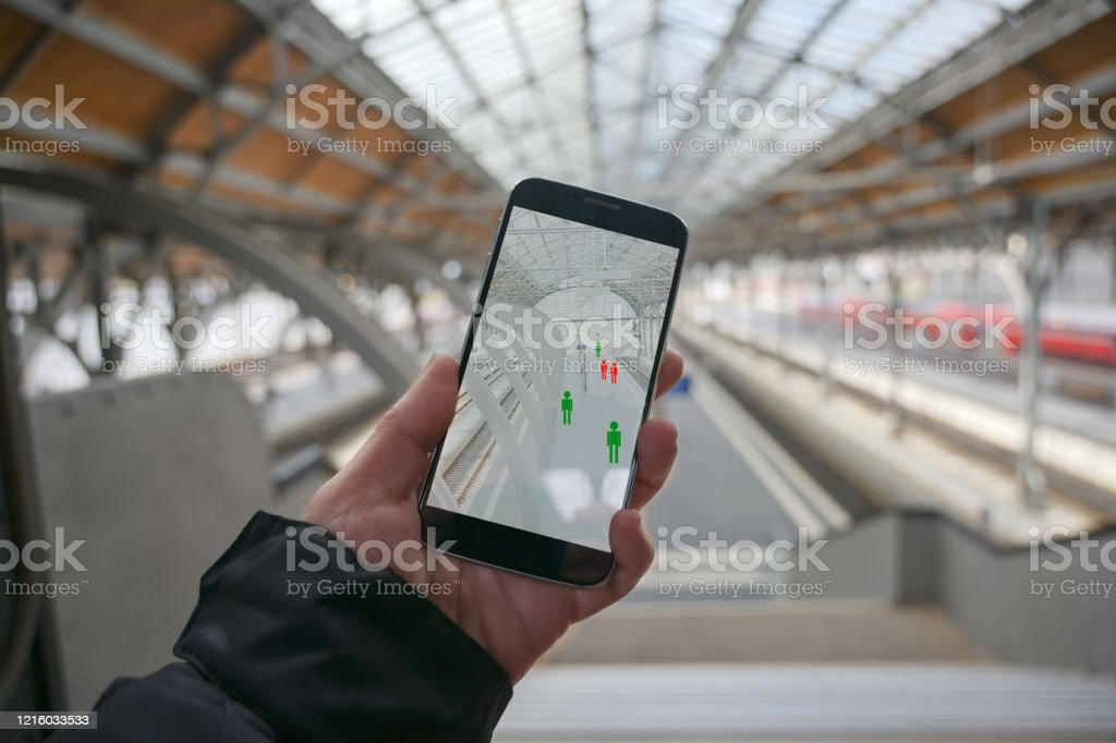 Older hand with a smartphone app for tracking the spread of infection which determines the contact persons of people who have been infected with the coronavirus, train station blurry in the background, copy space Older hand with a smartphone app for tracking the spread of infection which determines the contact persons of people who have been infected with the coronavirus, train station blurry in the background, copy space COVID-19 Stock Photo