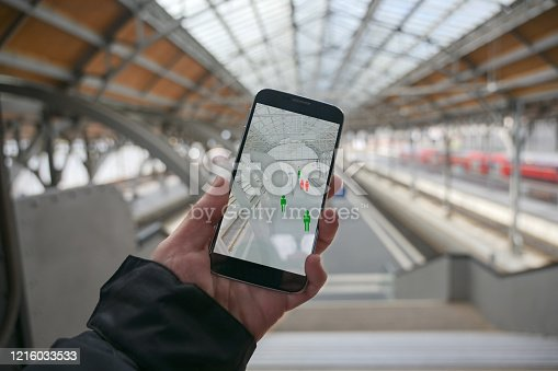 Older hand with a smartphone app for tracking the spread of infection which determines the contact persons of people who have been infected with the coronavirus, train station blurry in the background, copy space