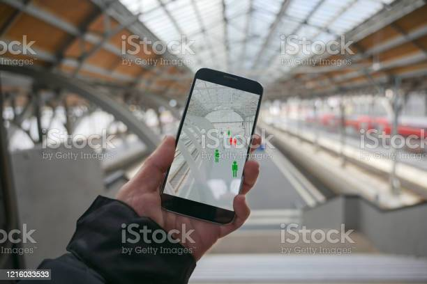 Older Hand With A Smartphone App For Tracking The Spread Of Infection Which Determines The Contact Persons Of People Who Have Been Infected With The Coronavirus Train Station Blurry In The Background Copy Space Stock Photo - Download Image Now