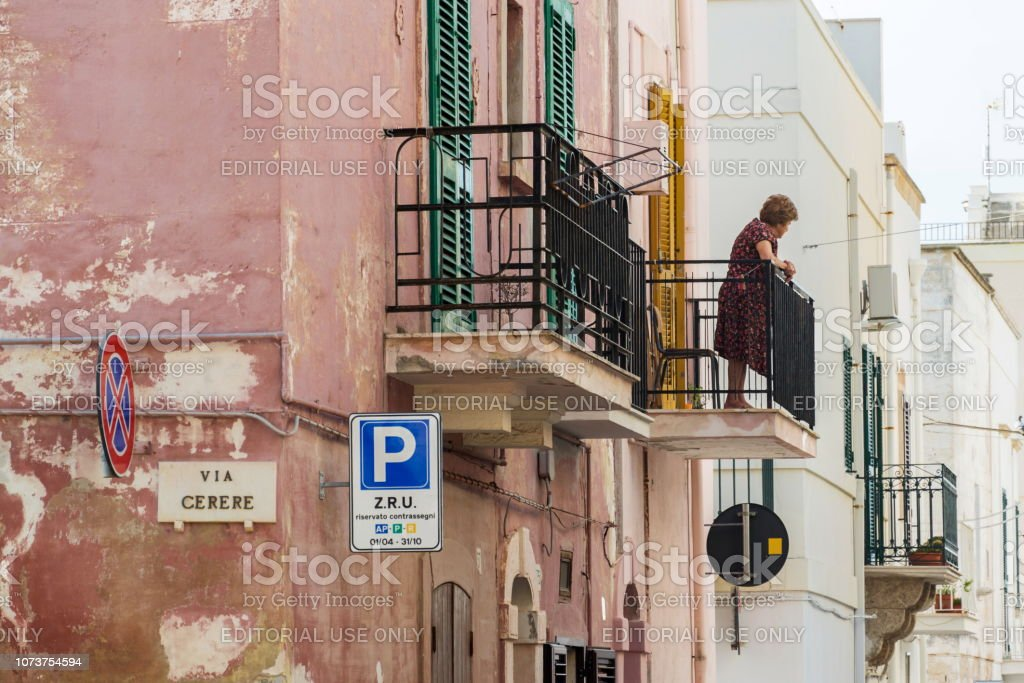 Older local woman looking to street from balcony in Polignano a Mare, Italy stock photo