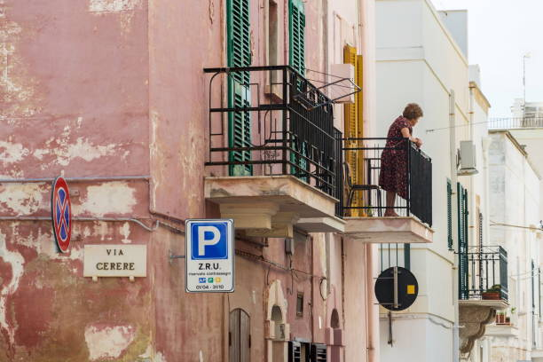 Mayores mujer mirando a la calle de balcón en Polignano a Mare, Italia - foto de stock