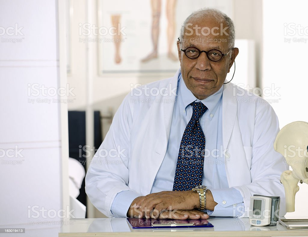 Older Male Doctor Sitting at His Office Desk royalty-free stock photo