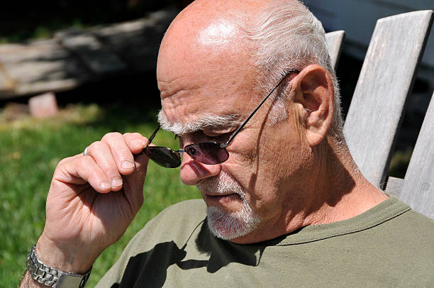 older man adjusts reading glasses - mike cherim stock pictures, royalty-free photos & images