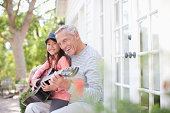 istock Older man and granddaughter playing guitar 167644132