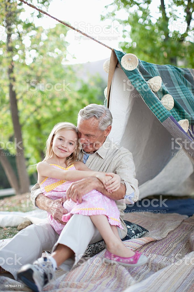 Older man and granddaughter relaxing outdoors royalty-free stock photo