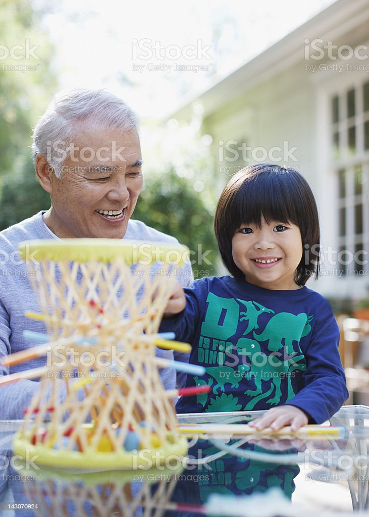 Older man and grandson playing together royalty-free stock photo