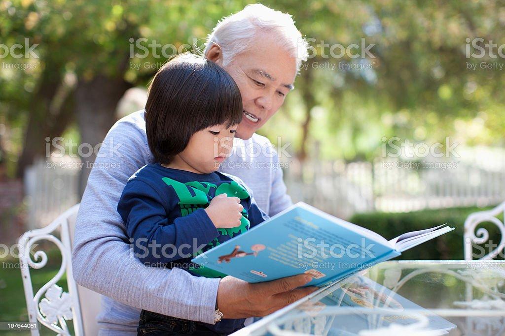 Older man and grandson reading together stock photo