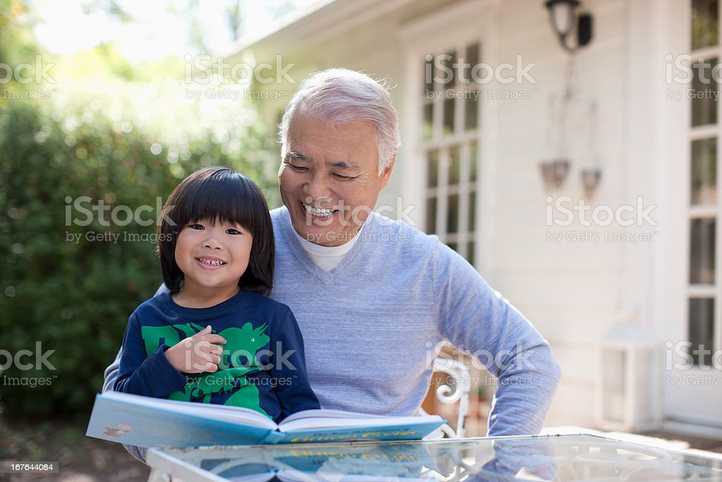 Older man and grandson reading together stock photo