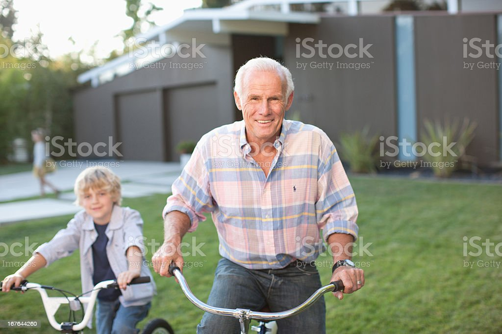 Older man and grandson riding bicycles outdoors royalty-free stock photo