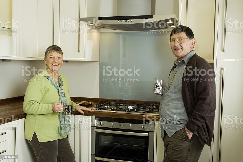 Older man and woman couple in modern kitchen royalty-free stock photo