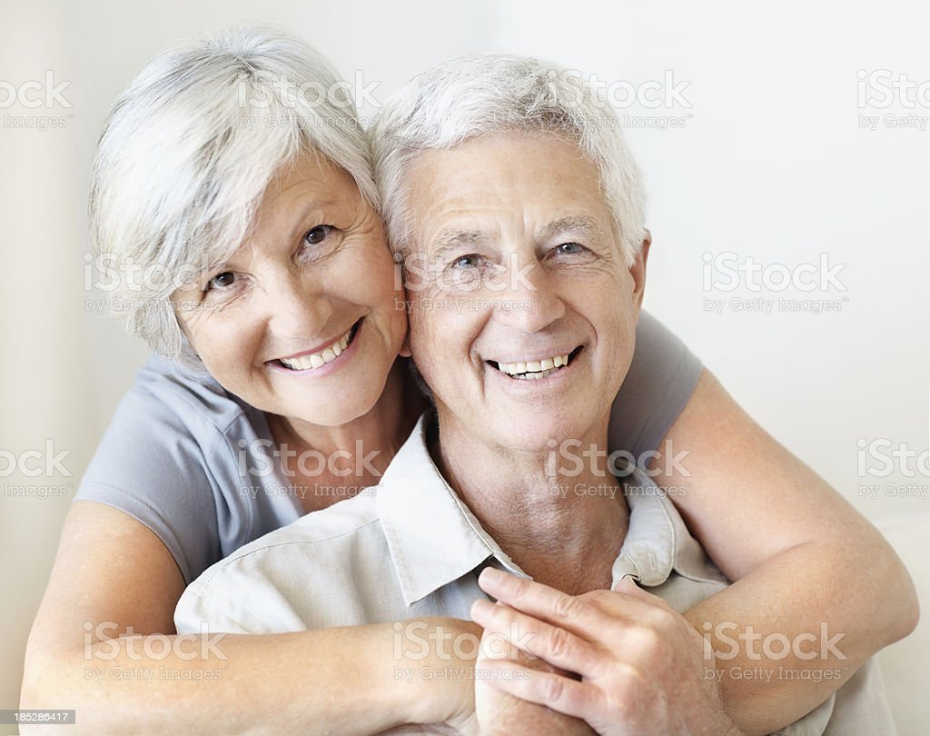 Older man and woman smiling and embracing stock photo