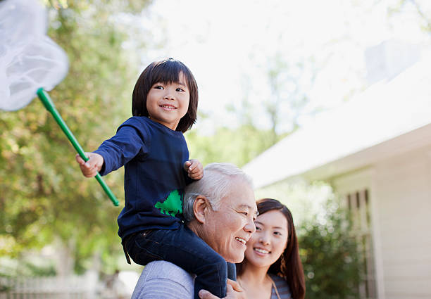 Older man carrying grandson on shoulders  old mother son asian stock pictures, royalty-free photos & images