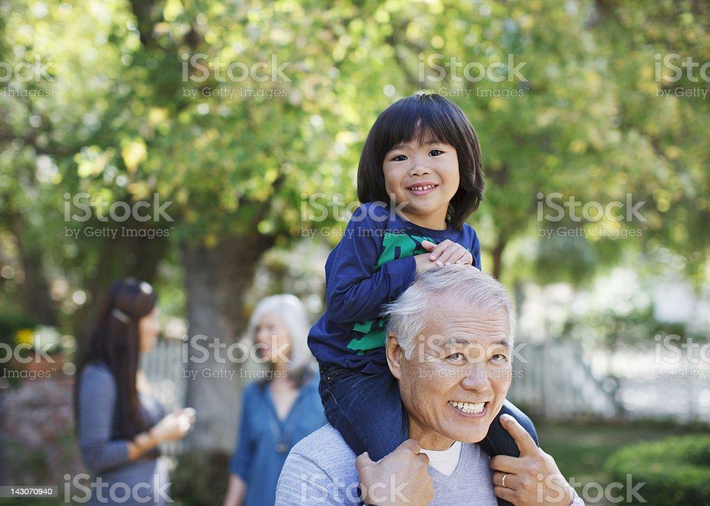Older man carrying grandson on shoulders stock photo