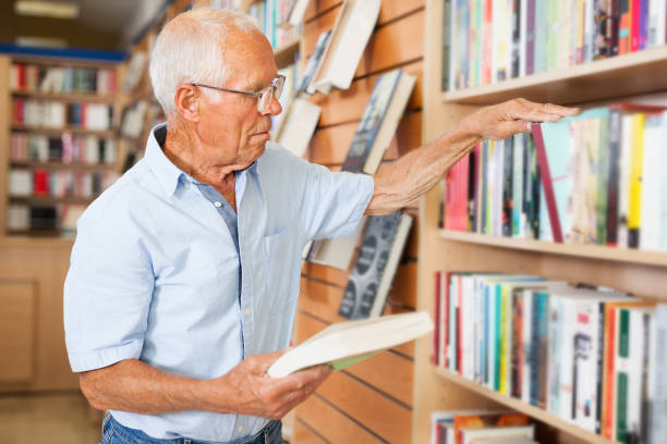 older man choosing books in bookstore - pensionati lavoratori foto e immagini stock