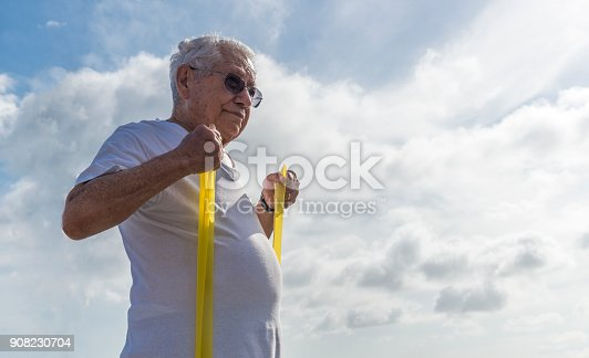 istock Older man (80-89) exercsing with a stretch cord at open air gym in Ipanema Beach, Rio de Janeiro, Brazil 908230704