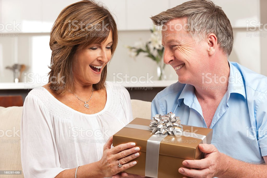 Older man giving his wife a beautifully wrapped gift stock photo