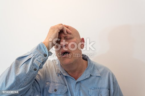 istock Older man hand to forehead in distress or pain, bald, alopecia, chemotherapy, cancer, isolated on white 920008244