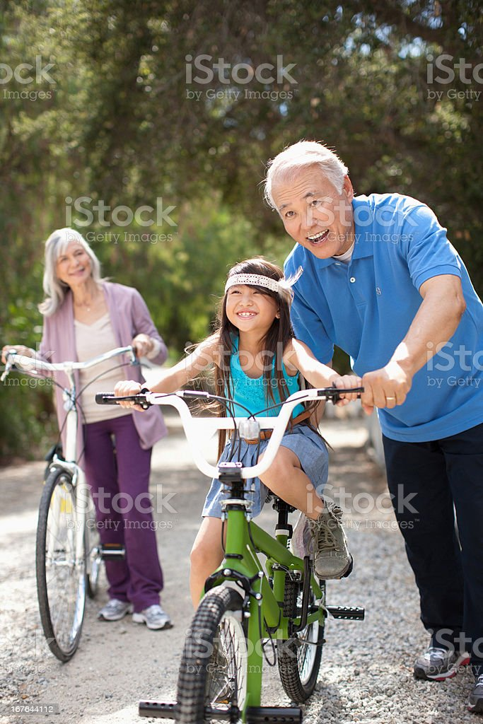 Older man helping granddaughter ride bicycle stock photo