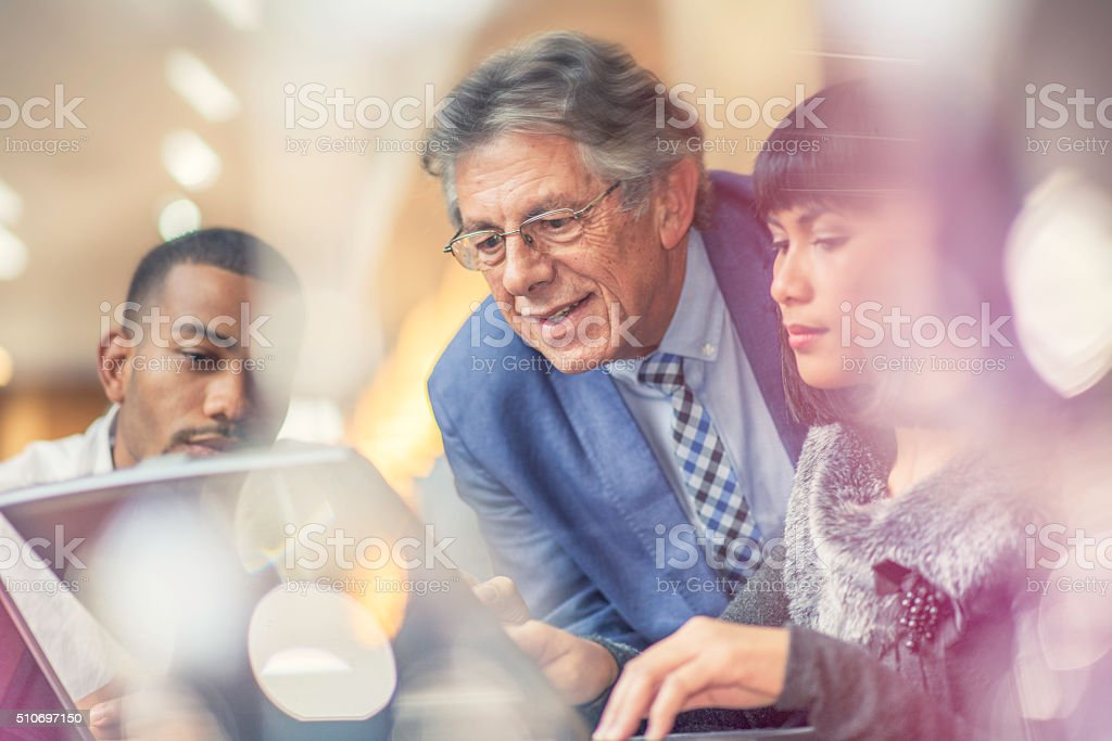 Older man helping his younger colleagues in a relaxed environment stock photo