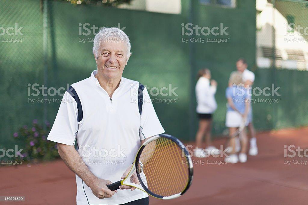 Older man holding tennis racket on court stock photo