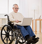 Older man in wheelchair shopping on Computer with credit card