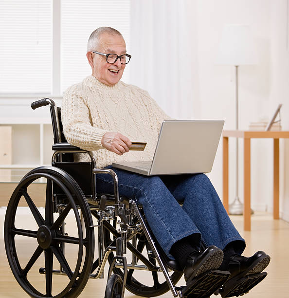 Older man in wheelchair shopping on Computer with credit card stock photo