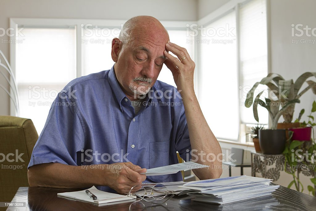 Older man looking frustrated while reviewing bills royalty-free stock photo