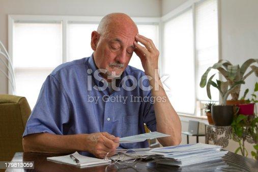 Older man frustrated while paying bills, horizontal