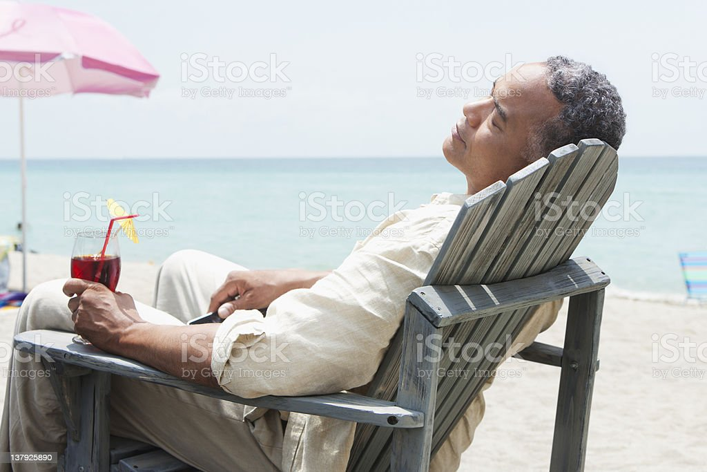 Older man lounging on beach chair with beverage royalty-free stock photo