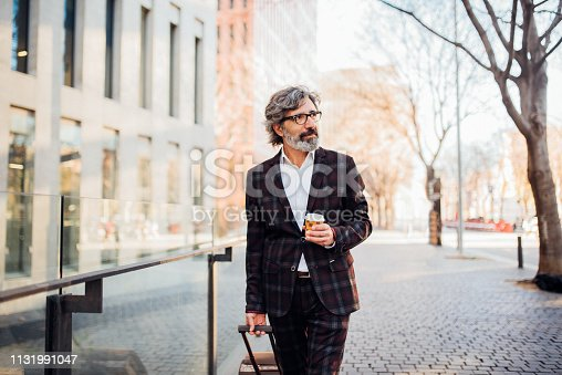 Man holding a cup of coffee while pulling his luggage