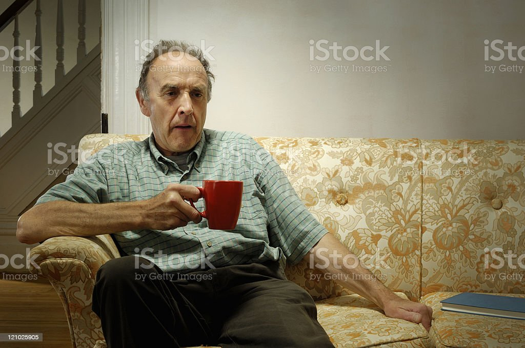 Older man on couch alone royalty-free stock photo