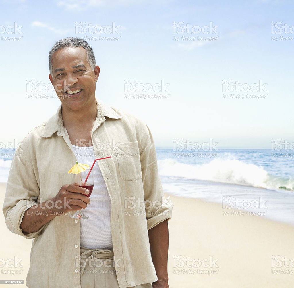 Older man on the beach with beverage royalty-free stock photo