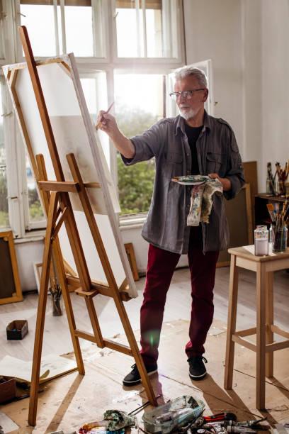 Older man painting stock photo