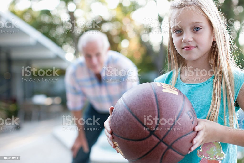 Older man playing basketball with granddaughter royalty-free stock photo