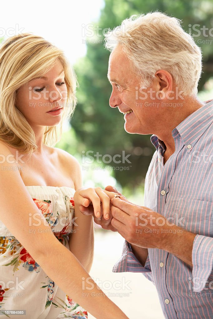 Older Man Proposing To Younger Woman stock photo