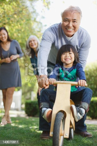 istock Older man pushing grandson in backyard 143070911