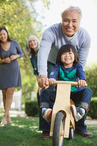 Older man pushing grandson in backyard  old mother son asian stock pictures, royalty-free photos & images