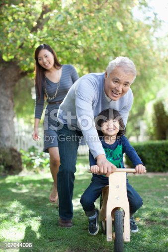 istock Older man pushing grandson in backyard 167644096