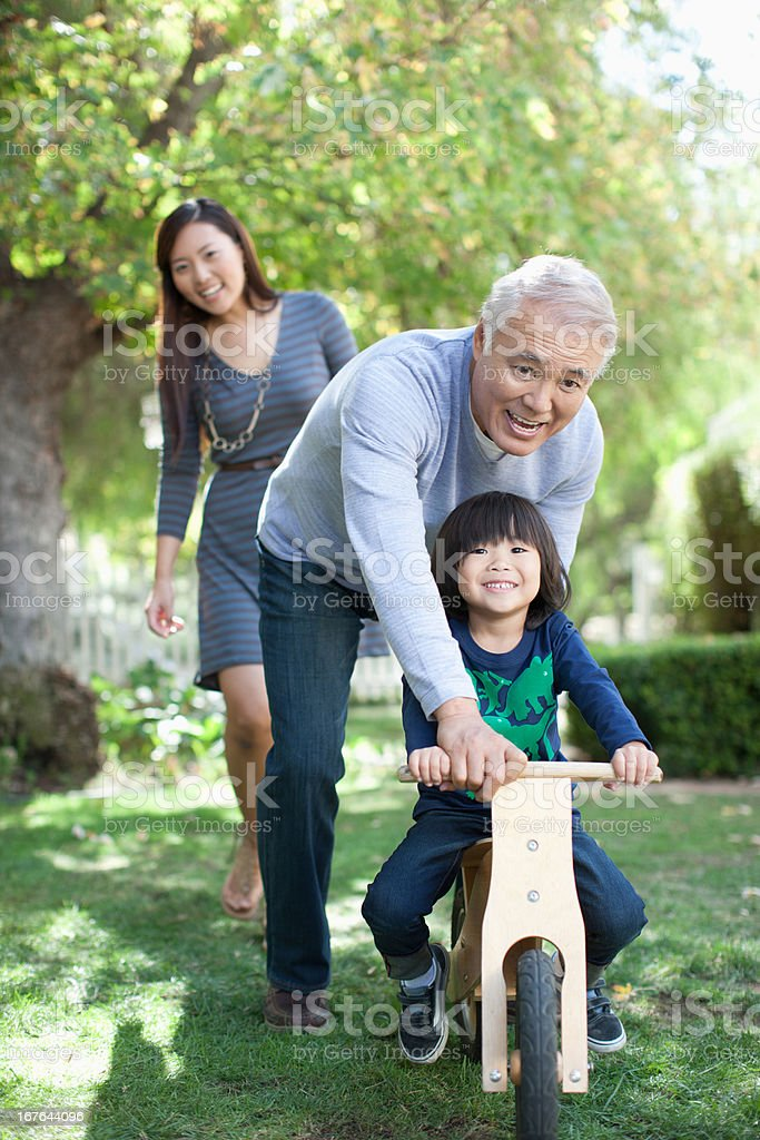 Older man pushing grandson in backyard stock photo