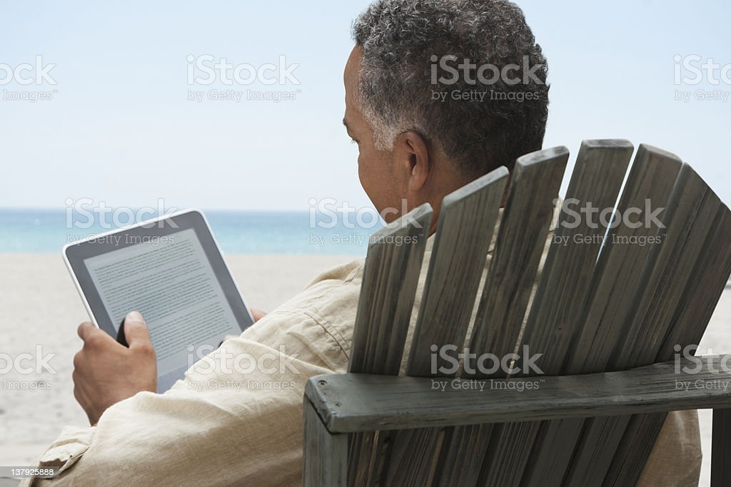 Older man reading on electronic tablet royalty-free stock photo
