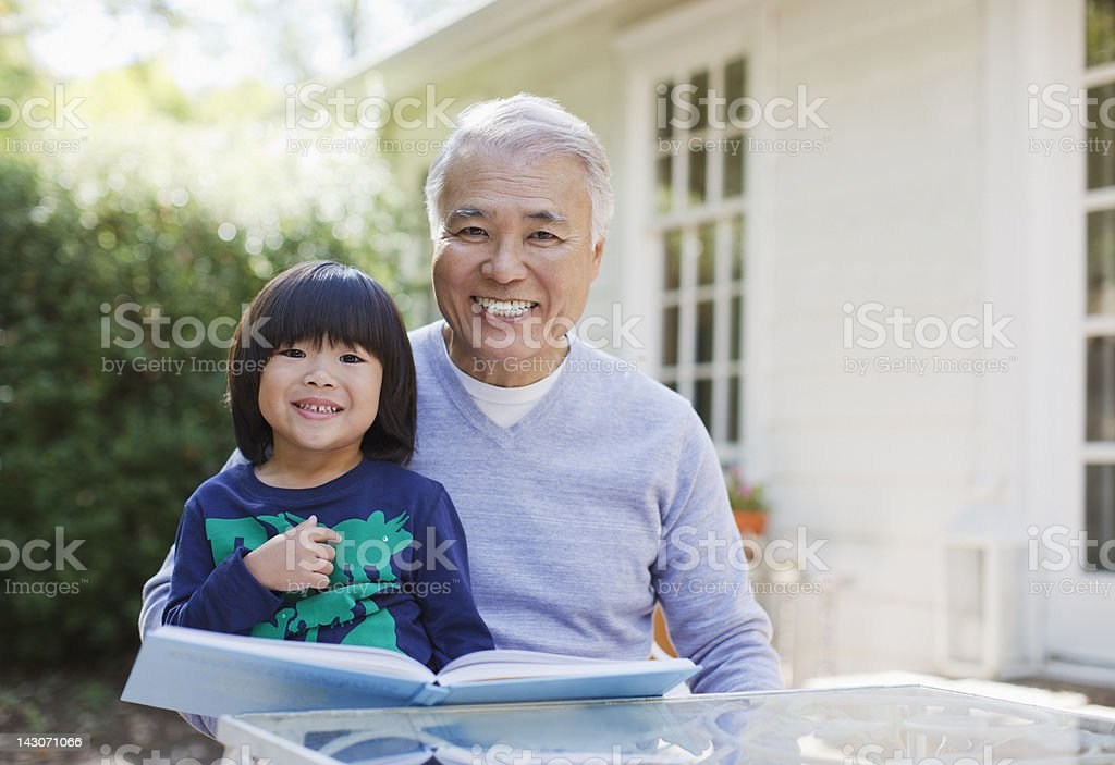 Older man reading with grandson outdoors stock photo