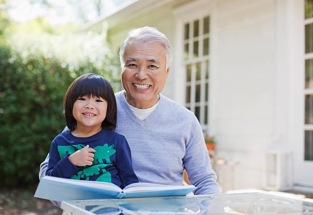 Älterer Mann liest mit Enkel im Freien – Foto