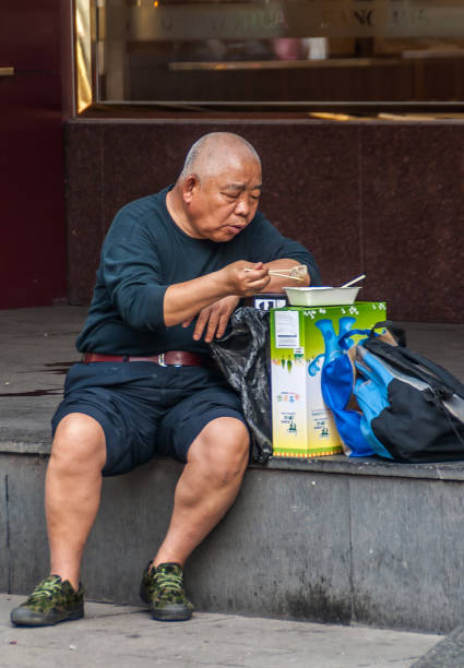 Older man sits on sidewalk eating his lunch, Shanghai, China. stock photo
