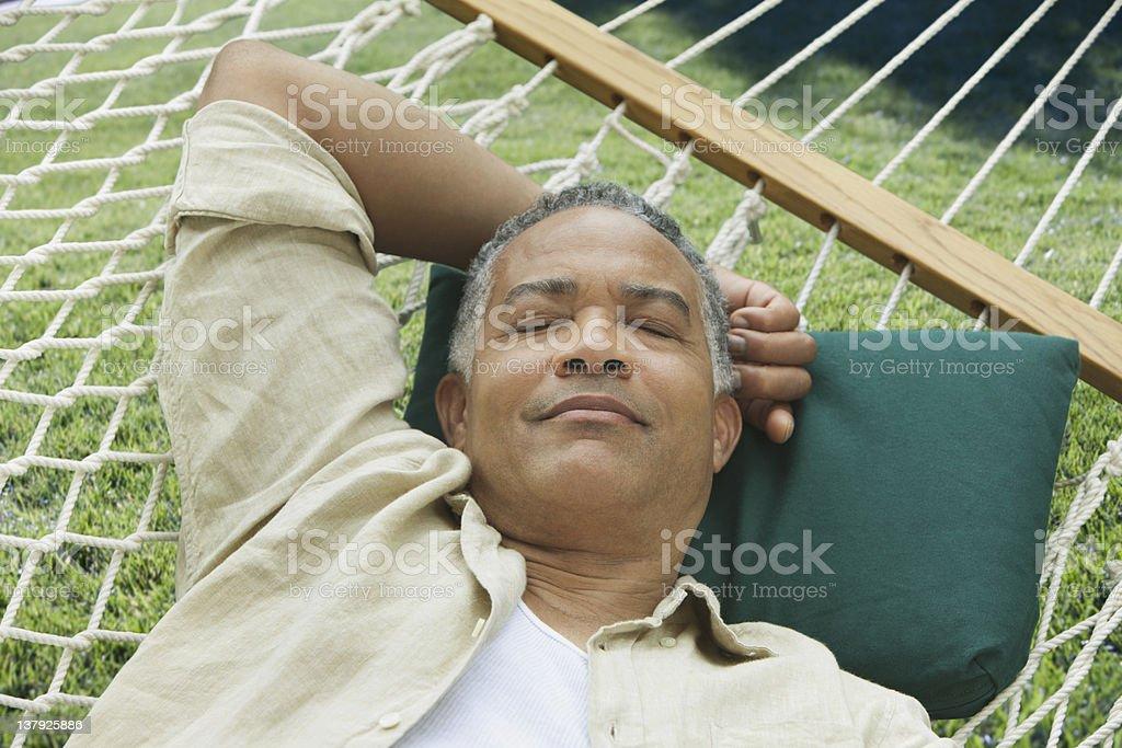 Older man sleeping on a hammock stock photo