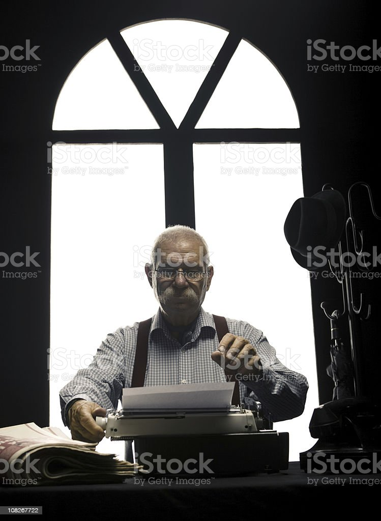 Older Man Typing on Typewriter at Desk with Newspapers royalty-free stock photo