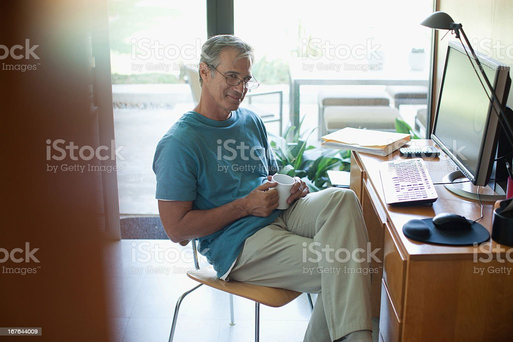 Older man using computer indoors royalty-free stock photo