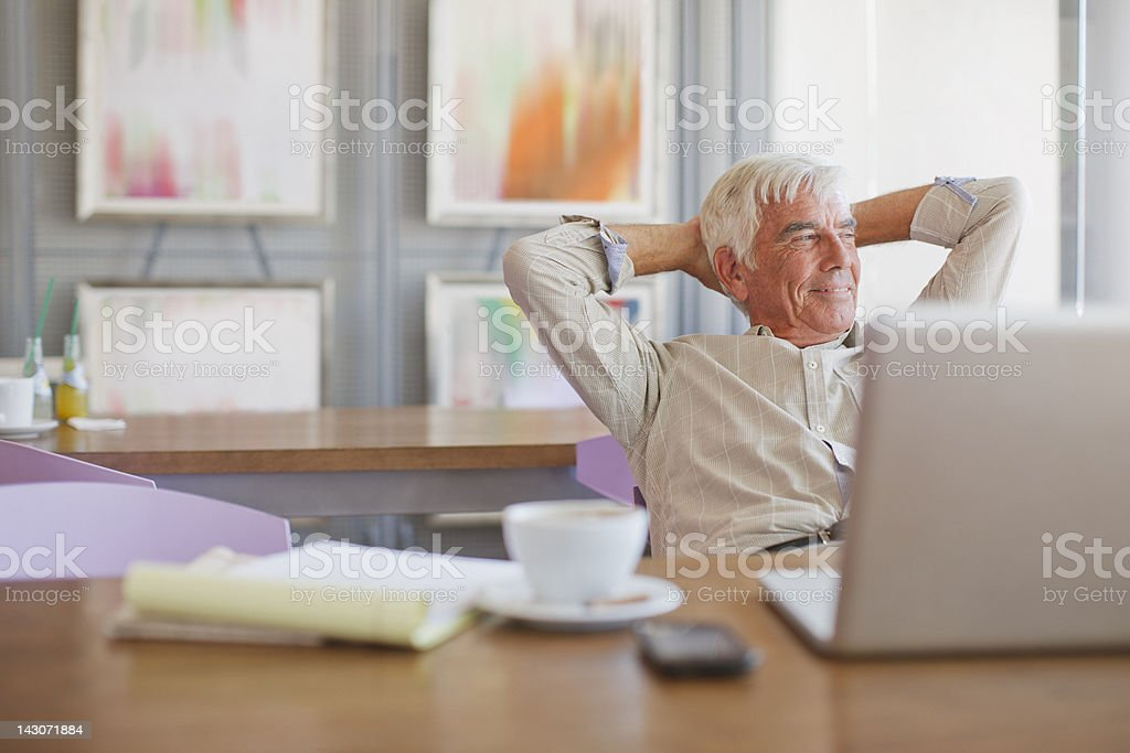 Older man using laptop in cafe stock photo