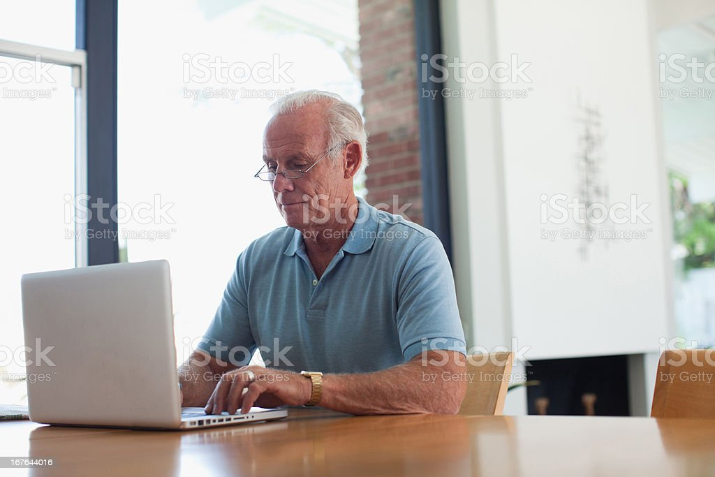 Older man using laptop indoors stock photo